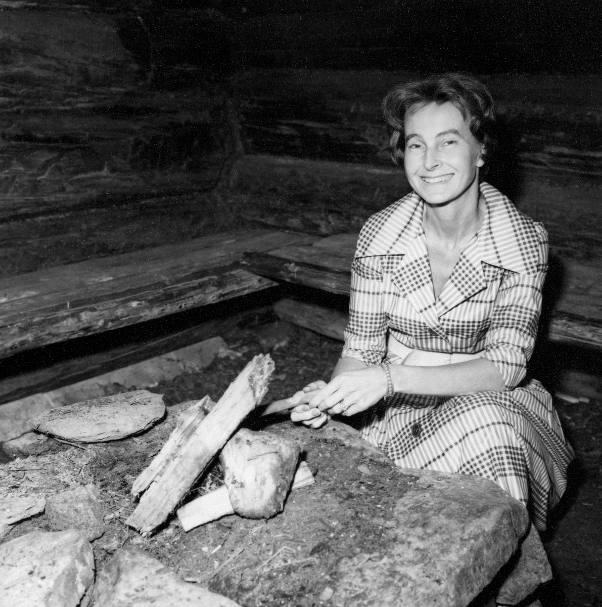 Arkeologen Anne Stine Ingstad (1918-1997 – født Anne Kristine Moe), fotografert i den såkalte «bjønnbua» fra Stor-Elvdal i Norsk Skogbruksmuseums friluftsmuseum på Prestøya i Elverum.  Ingstad var konservator ved dette museet fra 20. juni 1960 til 1. mai 1961.  Dette var for øvrig den første stillingen hun hadde etter å ha avlagt magistergradseksamen med avhandling om en steinalderboplass hun sjøl hadde undersøkt.  I 1960-61 var Anne Stine Ingstad Norsk Skogbruksmuseums eneste ansatte, men styreleder Magne Midttun var bosatt i Elverum og bisto også i den daglige driften av museet.  Ingstads arbeidsinnsats ved museet ble først og fremst preget av samlingsbyggende aktiviteter.  Hun samlet og registrerte gjenstandsmateriale og fikk utvidet bygningssamlinga i friluftsmuseet på Prestøya med ei kjøyte (jordkoie) fra Drangedal i Telemark og ei fiskebu med tilhørende naust fra Breisjøen i Alvdal.  Anne Stine Ingstad var også redaktør for museets andre årbokutgivelse, der hun selv bidro med en artikkel om reip av furupert, samt korte orienteringer om husværene fra Breisjøen og et par interessante gjenstander som var registrert inn i samlingene.  Ingstads begynte ved Norsk Skogbruksmuseum i en tidsbegrenset engasjementsstilling, og hun sluttet fem måneder før engasjementets avtalte utløpsdato for å slutte seg til ektemannen, Helge Ingstad (1899-2001), som under leting etter spor etter norrøne nybyggere på Nord-Amerikas vestkyst, oppdaget tufter på L'Anse aux Meadows på Newfoundland.  Anne Stine Ingstad ledet det arkeologiske undersøkelsene av denne vikingtidslokaliteten i perioden 1961-1967, og fikk seinere doktorgrad i faget sitt med rapporten fra disse utgravingene som avhandlingsarbeid.  I en stilling som statsstipendiat arbeidet hun seinere med publikasjoner om brukstekstilene fra Osebergfunnet og om tekstilfunnene fra kollegaen Charlotte Blindheims (1917-2005) vikingtidsutgravinger på handelsstedet Kaupang i Vestfold i andre halvdel av 1950-åra.  Anne Stine og Helge Ings
