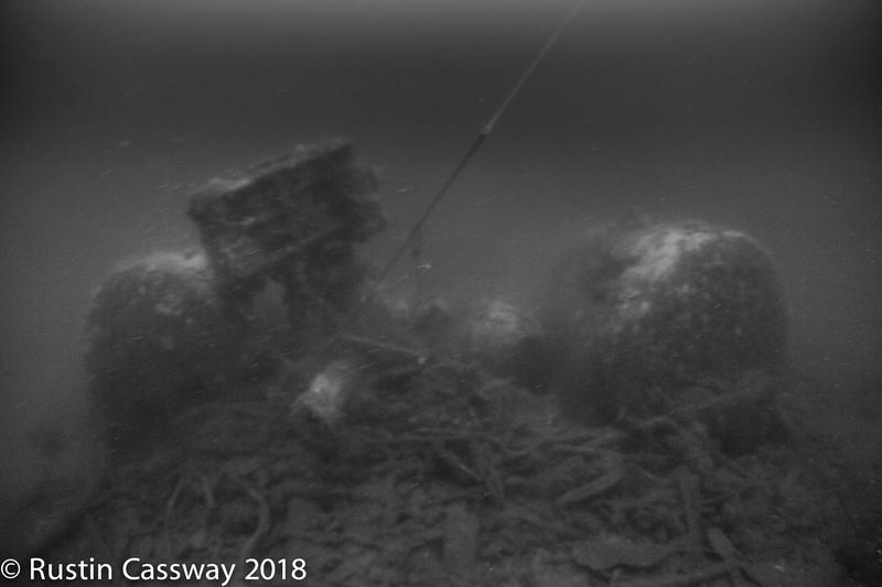 Uklart svart-hvitt bilde av dampkjeler på skipsvrak under vann.