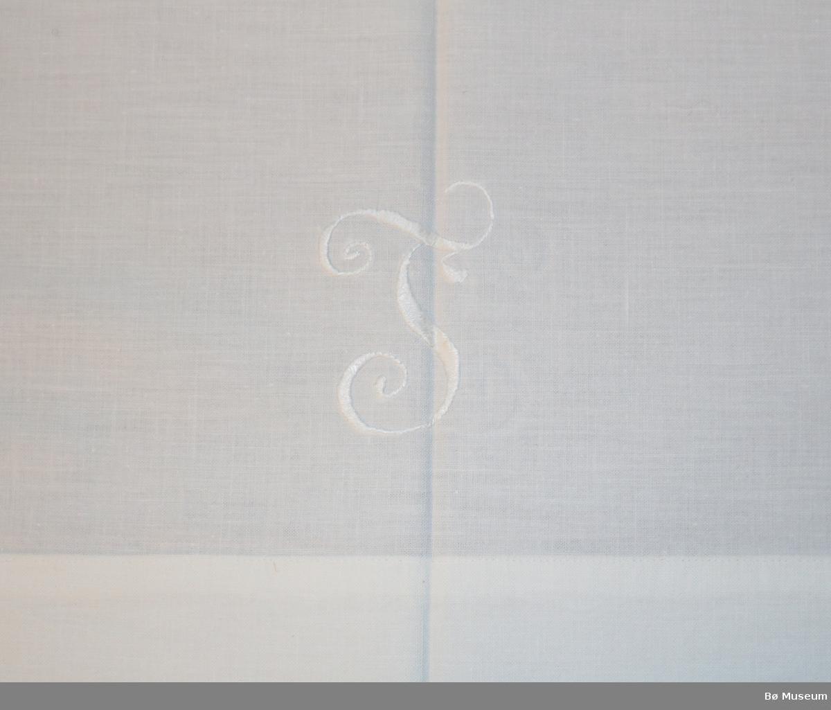 Bomullslaken med fall i begge kortsidene. Jare i begge sider. Kvit brodert L midt på, nederst.