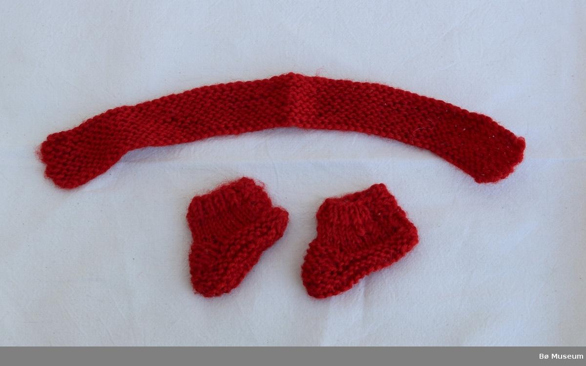 Strikka skjerf (a) og to sokkar/tøflar (b og c) til dokke. Det er eit hol i den eine sokken (b).