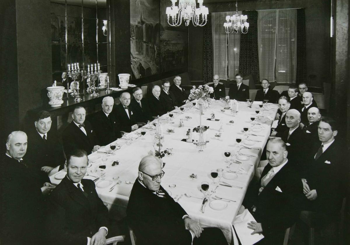 Avskjedsmiddag for Justitiarius Jørgen J. Stavig. En gruppe menn rundt et dekket bord.