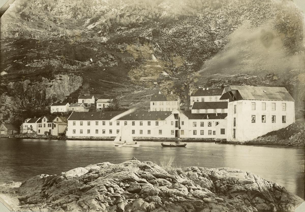 """Salhus Tricotagefabrikk sett frå sjøen, mellom ca. 1880-1895. Salhus Tricotagefabrik i Salhus omkring 1880. Heilt til høgre er kolhuset der kolskutene la til. Kolet blei heist opp i tønner til 2.etasje, der det blei tømt over i trillebårer og køyrt til kolbingen.   Til høgre bak fabrikkbygningen ligg skulehuset frå 1878. Det ligg arbeidarbustadar framfor og til venstre for skulehuset. I """"1860-boligen"""" til venstre budde jenter på loftet og familiar i leilegheitene i etasjane under. Nede ved sjøen til venstre i biletet ligg smia og huset til Johannes Vedå, som til seinare vart smed i Salhus Væverier. Deretter ser vi huset der """"Hilda-butikken"""" kom seinare. Dei fire husa bak desse var av dei eldste i Salhus."""