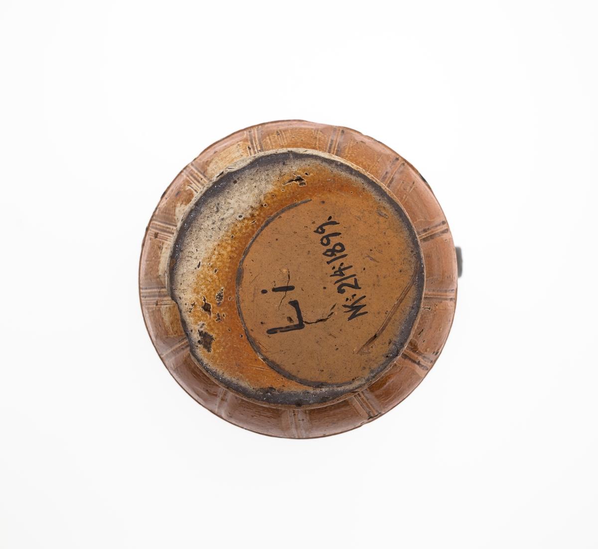En frise med dansene bønder på korpus. Ni par og en enslig. Dette motivet har sin opprinnelse i kopperplategraveringene til Nürnbergmesteren Hans Sebald Beham (1500-1550), og var et av de mest populære motivene på raerenkanner på 1500-tallet. Rundt halsen en symetrisk komponert, ornamental frise med motiver i følgende rekkefølge: solsikke, arabesk, sol med ansikt, arabesk, solsikke. På korpus øvre cavetto et bånd med ogivaler eller løv. På korpus nedre cavetto et bånd med rektagulære felt.