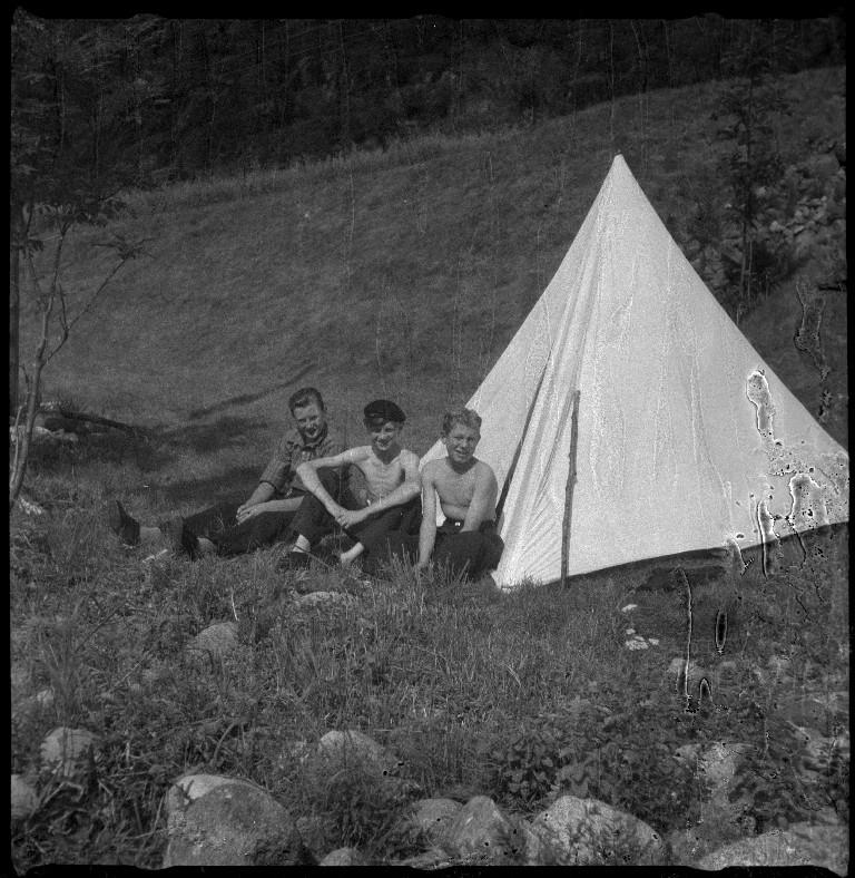 """Styrhuset til lastebåten """"Zita"""" i fart, med grus eller sand ombord. Det er også bilder av familien Skjold og tre gutter foran et telt. På bilde nr. 5 er Frida Johannessen nr. 2 fra venstre."""
