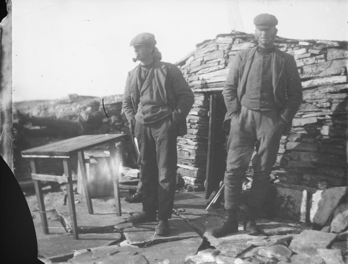 Tre mannfolk står ute ved ei steinbu