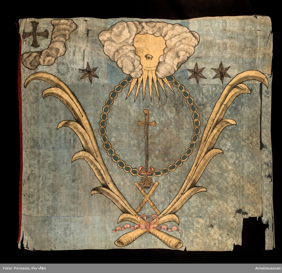 Duk av blå kinesisk sidendamast. I dukens övre del ett moln som omgärdar ett öga i ett gyllene fält. Under molnet ett svärd inom den ryska St Andreas orden i målad guldkedja. Allt inramas av palmblad i halmgul sidendräll nedtill hopknutna med rosa band. I stångsidans övre hörn ett kors inom ett moln. Tre gyllene stjärnor markerar vilket kompani fanan hör till. Strumpa av rött kläde. Stången avkortad.