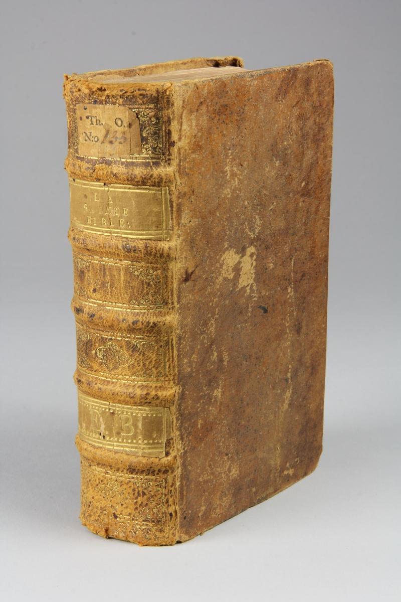 """Bok, helfranskt band """"La sainte bible traduite en françois sur la Vulgate"""", del 1. Skinnband med guldpräglad rygg i fem upphöjda bind, skuret rödstänkt snitt. Pärmarnas insidor klädda med marmorerat papper."""
