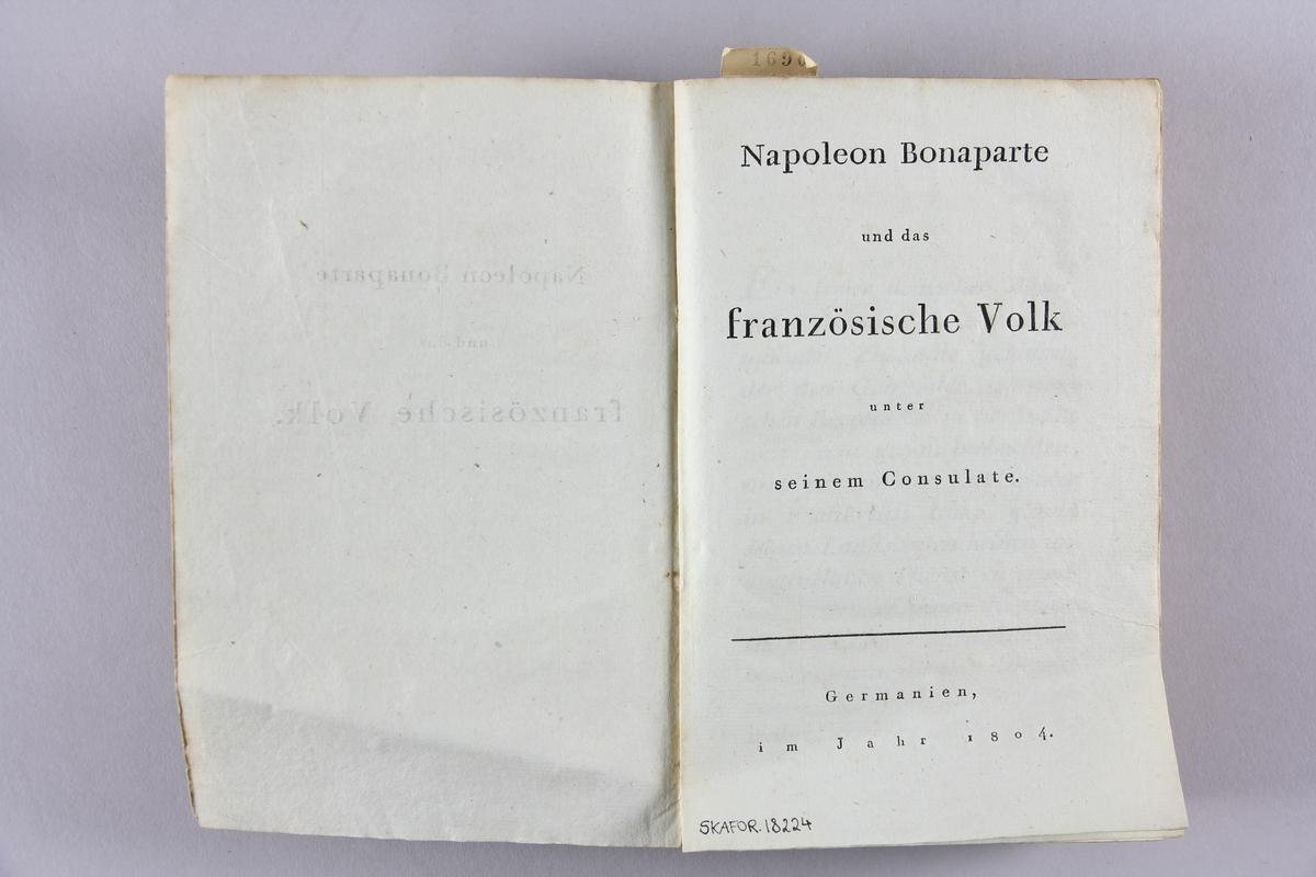 """Bok, häftad """"Napoleon Bonaparte und das französische Volk"""". Pärmar av gulbrunt papper. Rygg med tryckt titel samt etikett med samlingsnummer."""