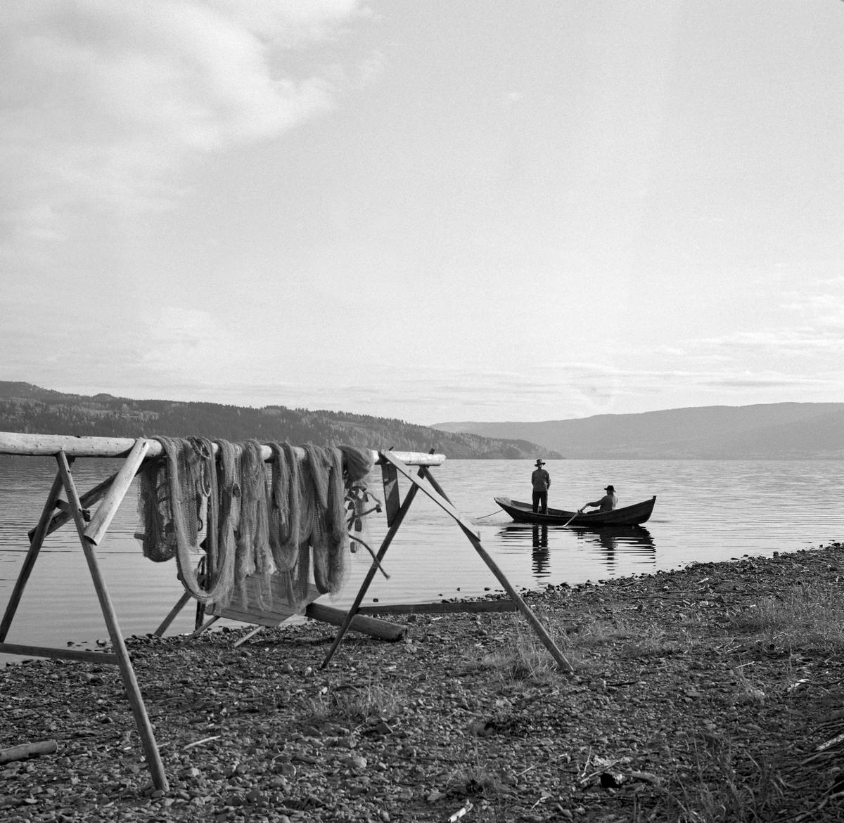 Lågåsildfisket. Sildenot til tørk på Borudodden. Notdraing. Bildet viser sildenot til tørk i forgrunnen, ellers ser vi to karer i ei åfløy som står og drar inn nota. Bildet er tatt i forbindelse med innspillingen av en film om lågåsildfiske i 1963.