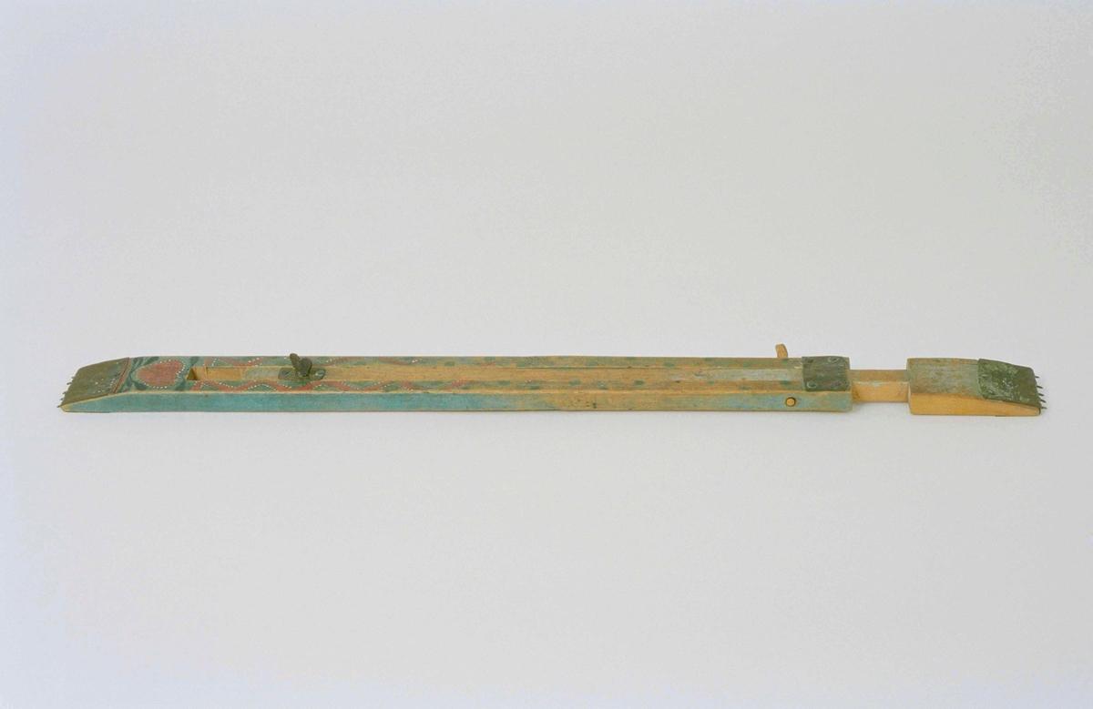 Vävspännare av trä, blåmålad med röd, grön och vit dekor. Består av två avlånga delar som är infogade i varandra. Med skruvanordning kan spännarens längd förkortas och förlängas. Delarnas slutstycken har metallbeslag med taggar. Används för att hålla ut den färdiga vävbredden.