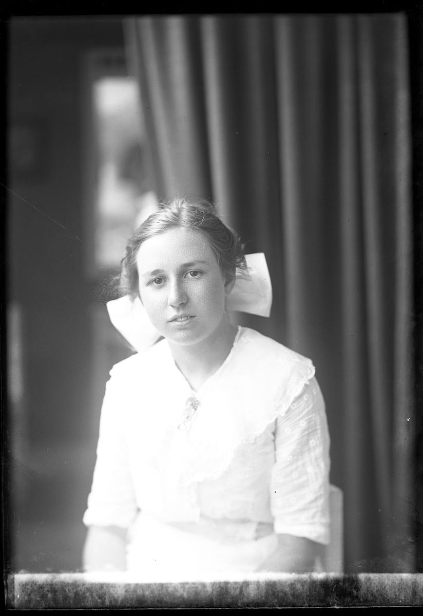 Porträtt av Lisa Tolstadius i vit klänning och vit rosett i håret.