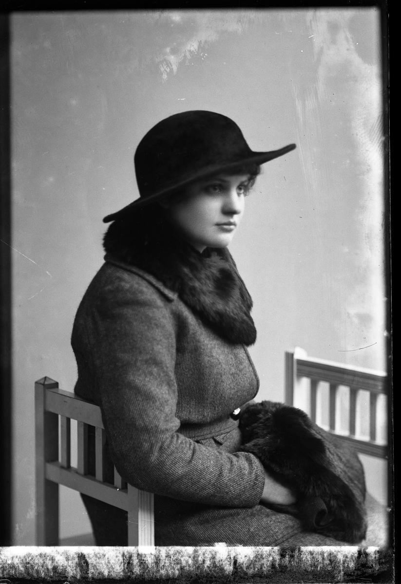 Porträtt av Vivan Hedlund sittandes på en pall och klädd i svart bredbrättad hatt, ytterkappa samt krage och muff i mörk päls.