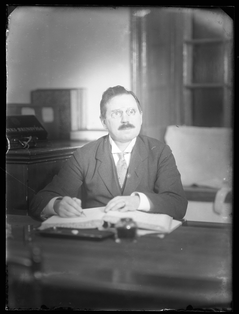 """I fotografens beskrivning står """"Hr. Petersén"""" men kan vara Petrus Vilhelm Petterssén, kontorist vid Alingsås Bomullsväveri. Porträtterad med bläckdon och bok."""