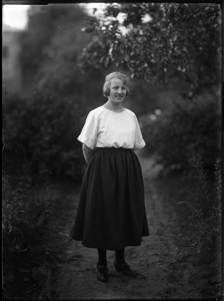 Porträtt av Agnes, klädd i mörk kjol och ljus blus, stående med händerna bakom ryggen i en trädgård.