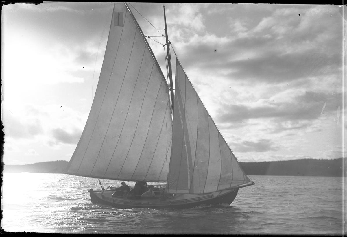"""Segelbåten """"Jolly"""" fotograferad vid kappsegling. Ombord finns tre personer."""