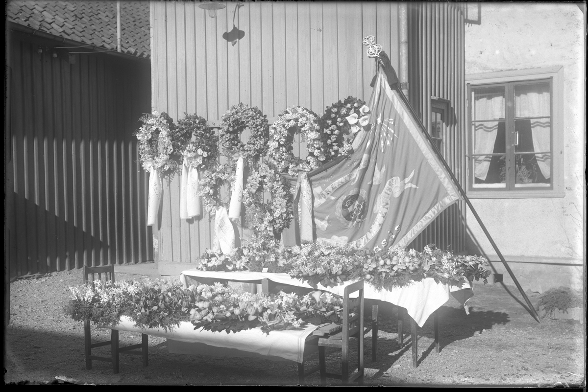 Blomkransar till Claes Perssons bår (se bild AM HO 00442). Kransar ligger på ett bord och en bänk samt hänger på väggen. Vid sidan står en stor flagga lutad.