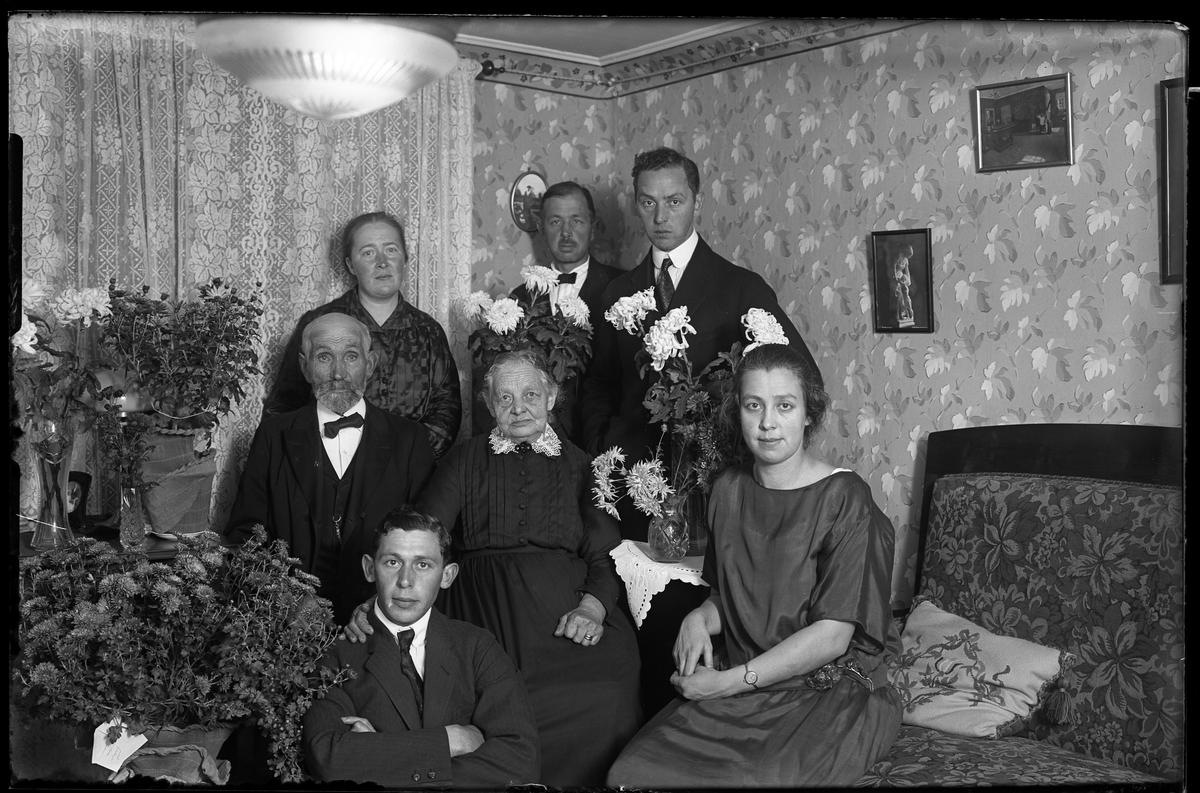 Familjeporträtt taget i samband med Svante och Ida Larssons guldbröllopsdag. Svante och Ida står längst bak tillsammans med deras ena son. På golvet sitter Hugo Larsson.