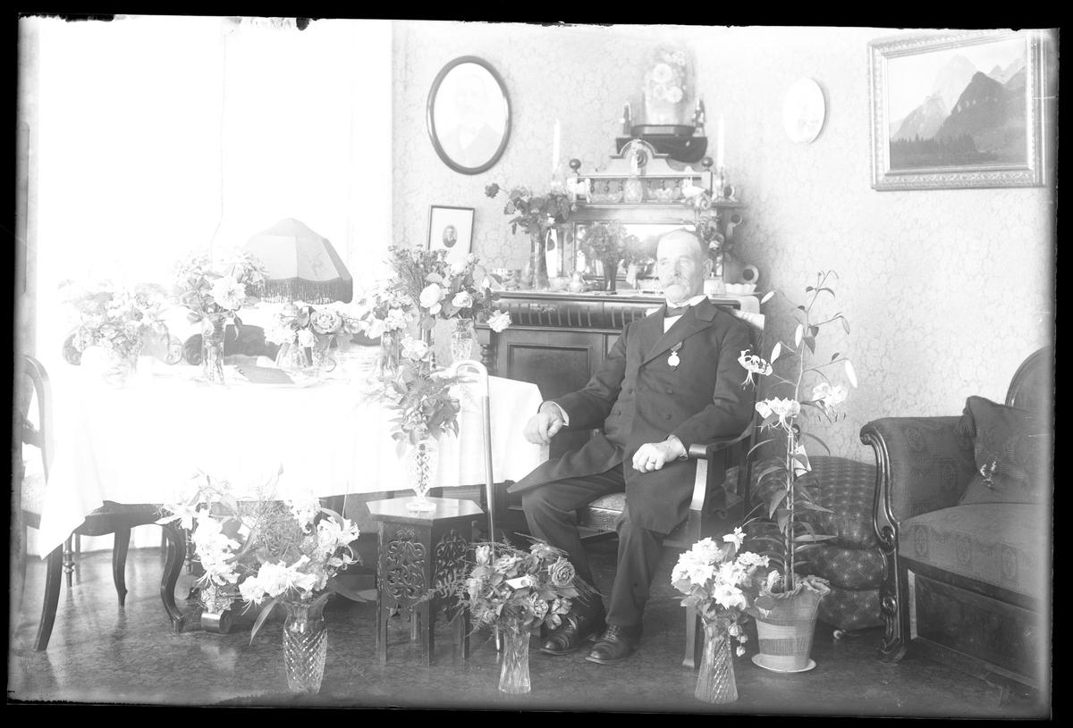 Victor Johansson fotograferad i ett finrum omgiven av blommor i samband med sin 60årsdag.
