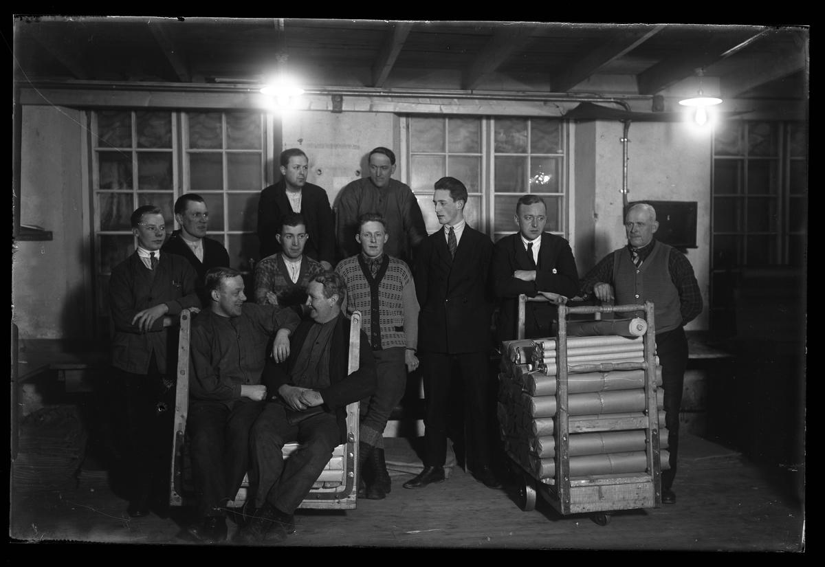 """Gruppbild på elva män med två vagnar packade med textilier fotograferad på Alingsås Bomullsväveri. I fotografens egna anteckningar står det """"""""Packargänget"""" Väveriet""""."""