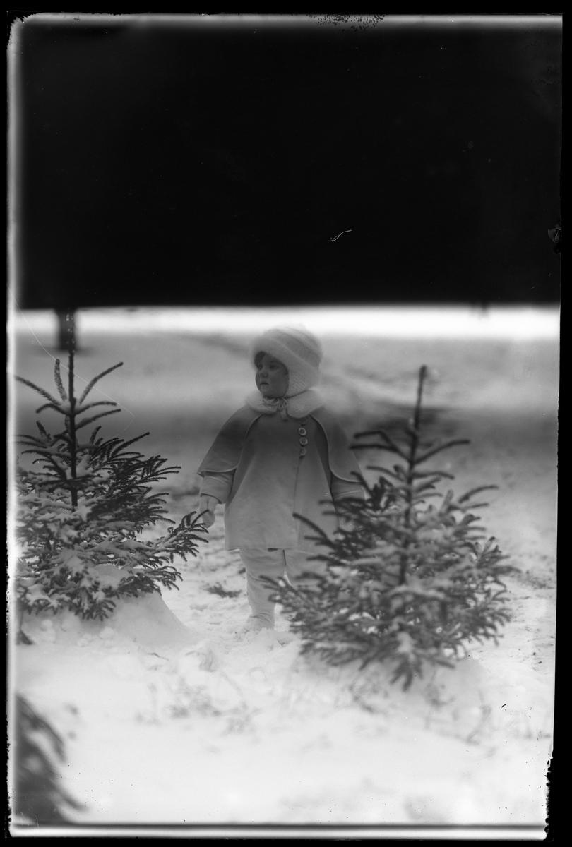 """En liten flicka, tolkad som Elsa Margareta Berg, i vita vinterkläder står i snön mellan två små granar. I fotografens anteckningar står det """"Ing[enjör] Bergs flicka"""". Bilden är inte helt exponerad."""