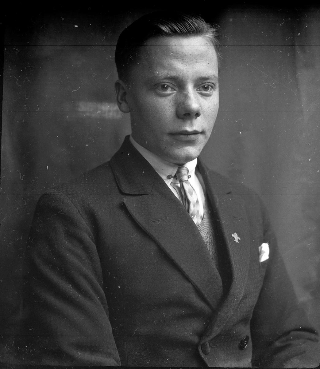 """Porträtt av en ung man med slips, skjorta, väst och kavaj. I fotografens egna anteckningar står det """"Åke Thorsell"""". Tolkat som Åke Gustaf Kristian Thorsell (f. 1911)."""