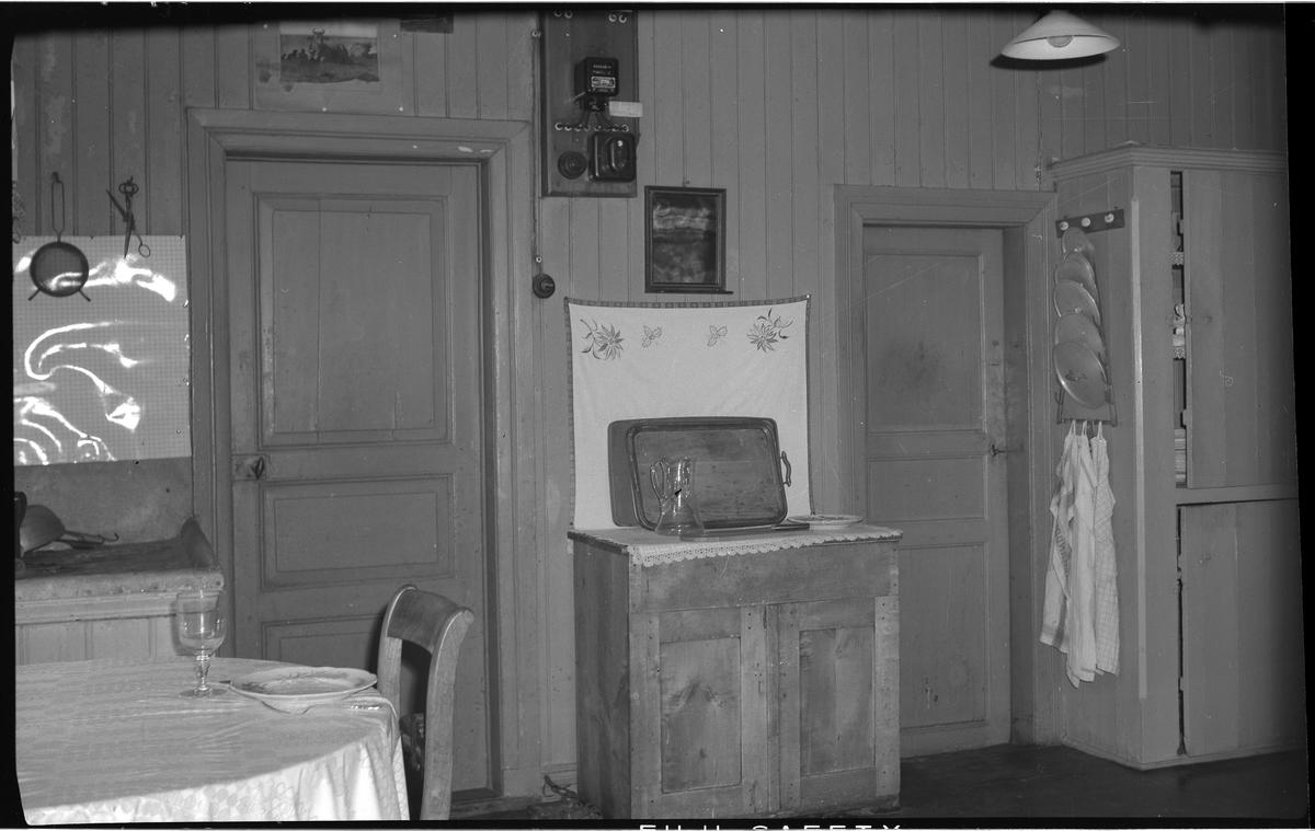 Interiör från en äldre bostadshus, villa Charlottenberg (Hedvigsberg) vid Göteborgsvägen. Huset byggt på 1800-talet. I köket. Bilden är tagen nästan rakt fram mot en av väggarna. Längst till vänster syns delar av den zinkklädda diskbänken, framför delar av ett matbord. På väggen bakom diskbänken är något blankt uppsatt, ett stänkskydd. Där hänger en sil och en sax. På bordet, som är runt, ligger en duk och det är framdukat ett dricksglas på fot och en tallrik och bestick. En stol står inskjuten under bordet, bara ryggen syns.  Till höger om diskbänken syns en ständ dörr med tre speglar. Till höger om dörren står ett lågt skåp med dubbeldörr och låda. På skåpet ligger en duk och bakom är en bonad uppsatt. Mot väggen och bonaden står en bricka av trä lutad och framför den en glaskaraff, och till höger står en tallrik. Ovanför bonaden hänger en liten spegel med en liten hylla. Ovanför spegeln, mot dörrkarmen, sitter en el-panel av något slag. Ovanför dörren sitter en bild med kossor.  Till höger om det låga skåpet finns ytterligare en dörr, den är mindre än den andra dörren och ligger längre in. Till höger om den lilla dörren är ett platsbyggt högskåp, klätt med samma panel som väggarna. På skåpets kortväggen sitter en krokbräda med tre krokar, på en hänger ett grytlocksställ med fem grytlock och nederst hänger tre handdukar. Skåpet är delat på mitten med två dörrar, dessa står lite på glänt.  I taket hänger en skomakarlampa.     Väggarna är klädda med stående panel.   Villa Charlottenberg (Hedvigsberg) på Göteborgsvägen.  Elin Bothén.  Foto 13 september 1966.