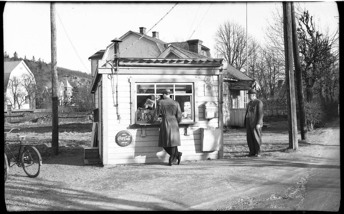 En liten träkiosk med liggande panel och ett stort, liggande, fönster eller lucka. Vid luckan står en man i trenchcoat och hatt. En annan man står vid sidan av, på höger sida.  I vänster kant ser man bakdelen av en cykel som står i ett cykelställ.  Bakom kiosken, i fonden, syns Häradsberget och framför, eller nedanför det, syns stora villor, ett med torn. Alldeles bakom kiosken syns flera bostadshus. Kiosken står i ett hörn av en tomt. Fotografen står vänd med ryggen mot järnvägsöverfarten och vägen till höger om kiosken är Boråsvägen, riktning mot Borås, och vägen till vänster är vägen mot Stockholm.  Centralkiosken på Boråsvägen 2 Innehavare Gunnar Risberg     Boråsvägen 2, april 1956 Boråsvägen 25, maj 1957  Innehavare Gunnar Risberg