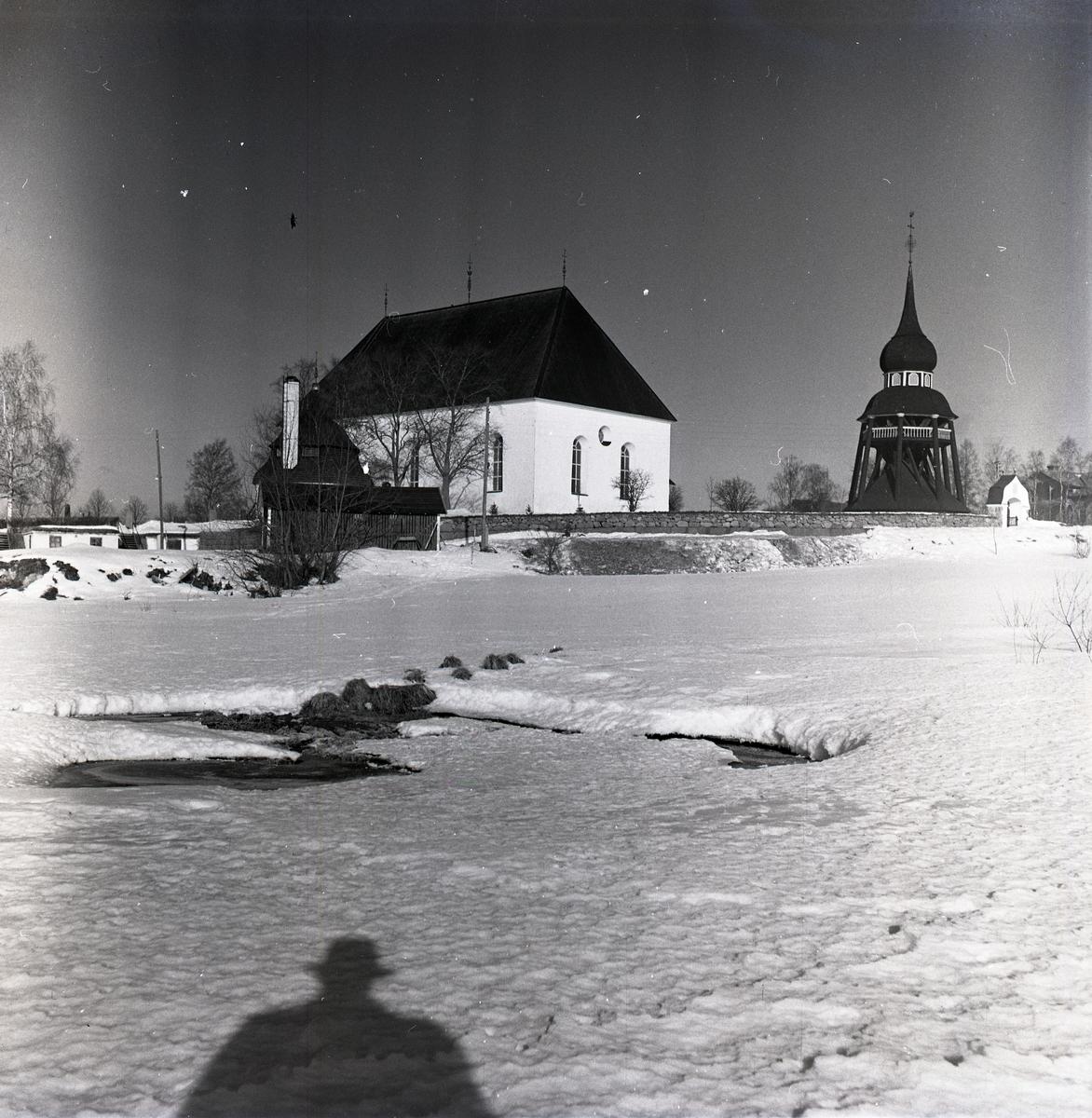 Ljusdals kyrka i vinterskrud med tillhörnade kyrktorn.