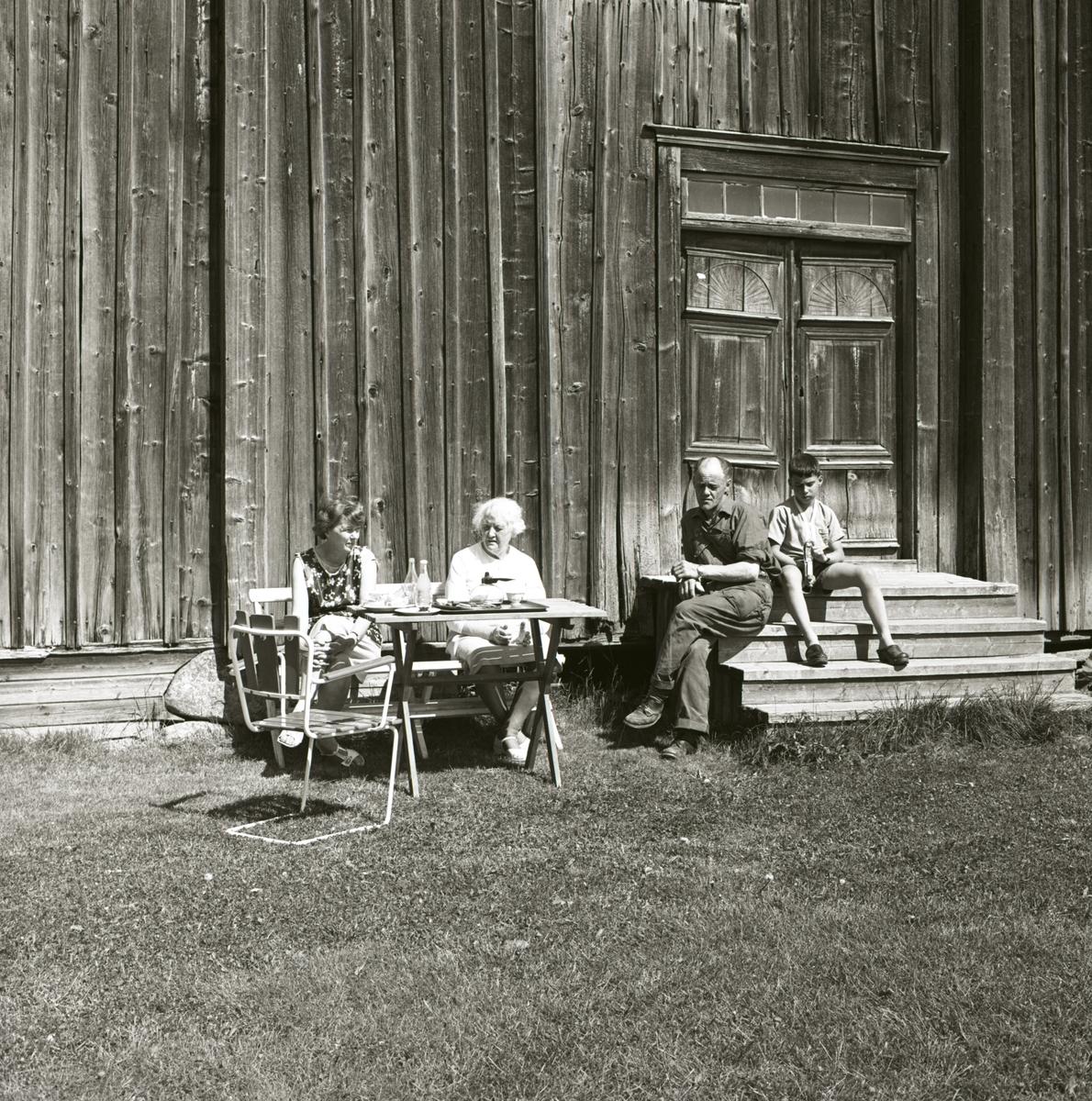 Två kvinnor sitter vid ett bord framför en byggnad och till höger om dem sitter en pojke och en man på en trappa, 1967-68.