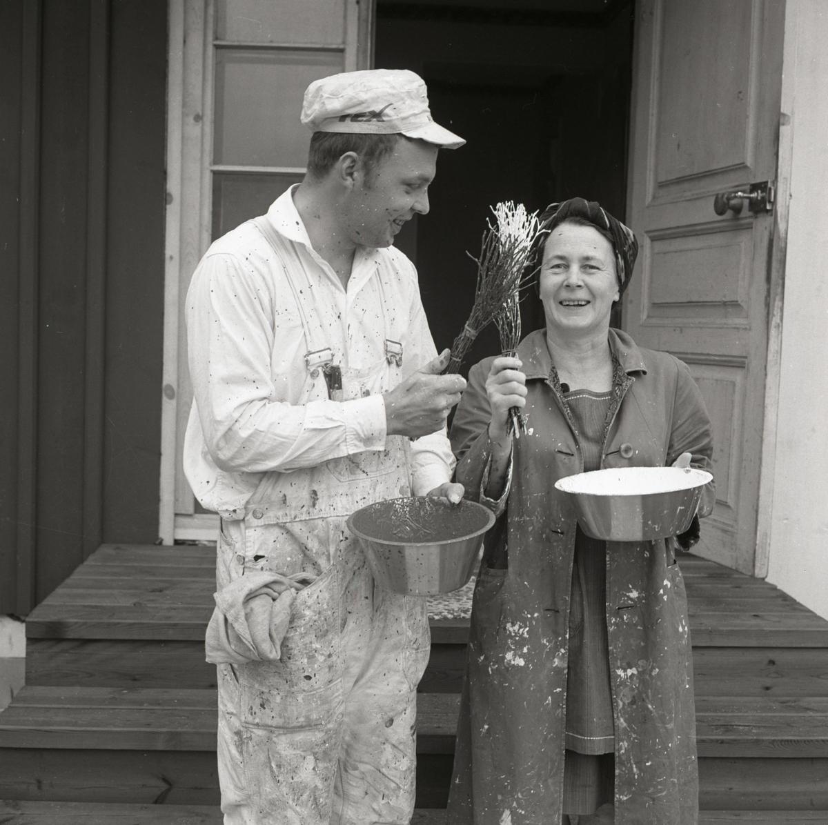 En kvinna och en man iförda målarkläder står framför en dörr och håller i en varsin borste, Sunnanåker 1967-68.
