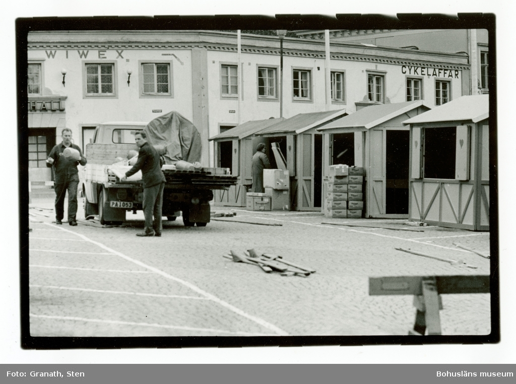 Kungstorget i Uddevalla. Två män lastar av flaket på en lastbil. Små bodar har byggts upp längs ena sidan av torget, troligen för försäljning. I bakgrunden syns saluhallens ingång och skyltar för Wiwex och en cykelaffär.