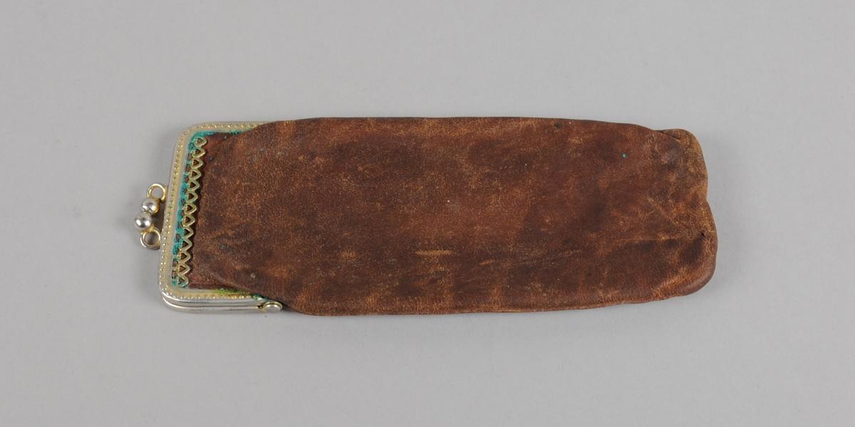 Brilleetui av skinn med kneppelås av metall på den ene kortenden. I etuiet ligger det en lorgnett.