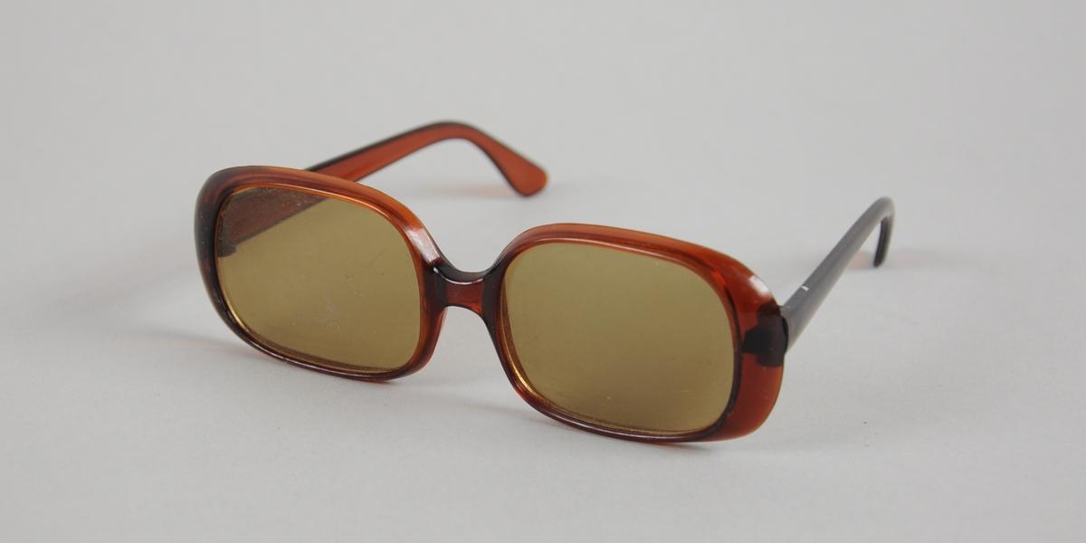 Solbriller med firkantede glass med avrundede kanter. Mørkebrun innfatning og brillestenger av plast.