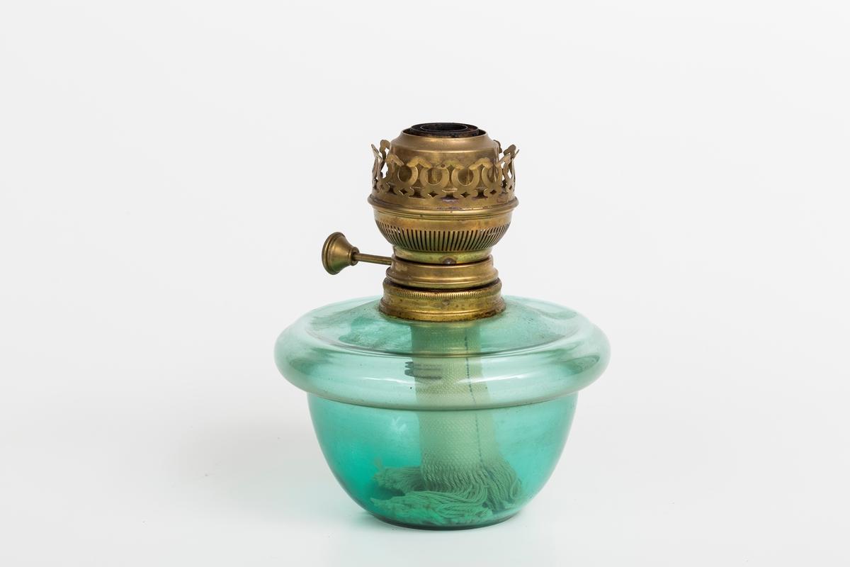 Parafinlampe i grønt glass med lampeglassholder i messing. Veke i lampen.