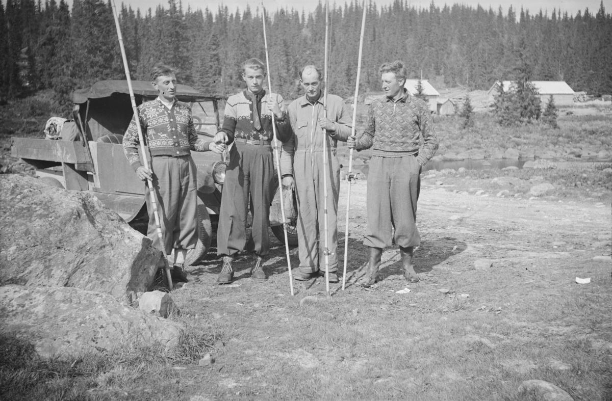 Fire menn på fisketur, fotografert foran en liten lastebil