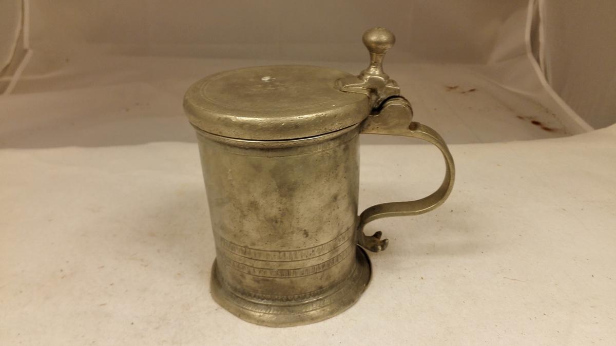 """Form: Sylindrisk. 1 tinkande.  Tinkrus av alm cylindrisk form. Har laag med knop. Hængslet i stykker og den nederste """"beit"""" defekt. Indvendig knopper ( pælemærker). Paa laaget indridset O.M. (Ole Mikkelsen Pladsen d.e.). Paa hanken Kandestöper Berent Steemans Stempel (för 1741).  Kjöpt av husmand Ole M. Pladsen, Amble.  (Loket er reparert i mars 1987)."""