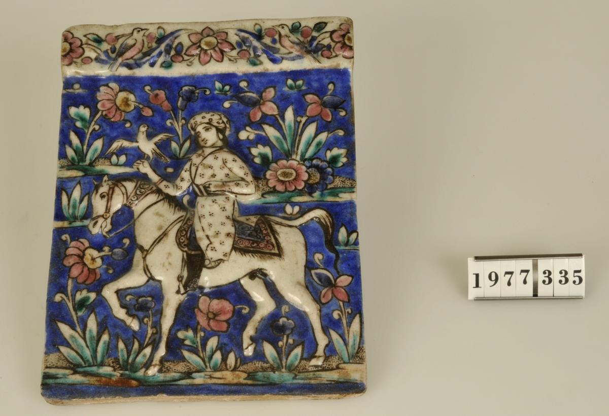 Rektangulärt glaserat kakel med målad dekor i flera färger. Motiv: Häst och ryttare, blommor, fåglar. Delvis utfört i relief.  Storlek: 15,5 x 21,4 cm.