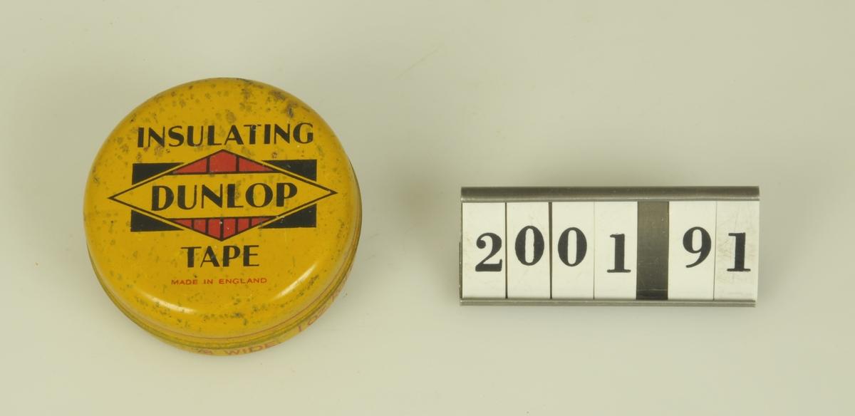 Rund gul ask. Text på engelska i rött och svart.  Har innehållit isoleringstape.