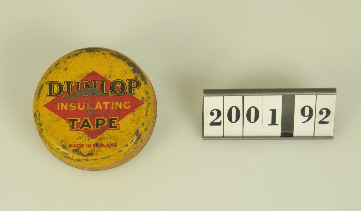 Rund gul ask. Text på engelska i rött och svart. Röd dekorationsrand längs lockets kant.  Har innehållit isoleringstape.