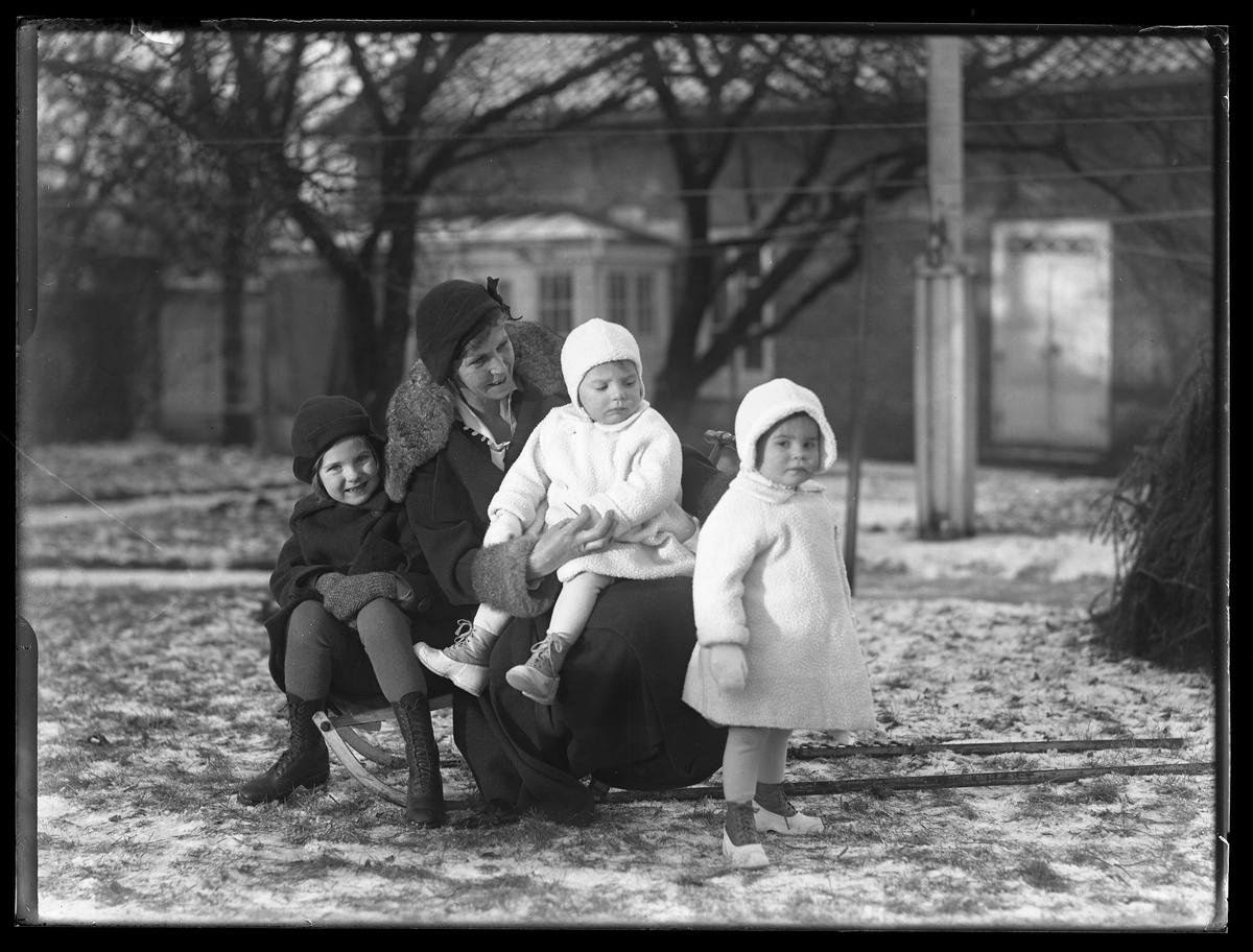 """En kvinna sitter tillsammans med två barn sitter på en kälke. Ytterligare ett barn står framför dem. De två yngsta är tvillingar och är klädda i vita vinterkläder medan deras äldre syster och kvinnan är klädda i svart. I fotografens egna anteckningar står det """"Ing.[enjör] Bergs barn"""", tolkat som tvillingarna Peter Wilhelm och Ulla Maria samt deras syster Elsa Margareta. Kvinnan är okänd."""