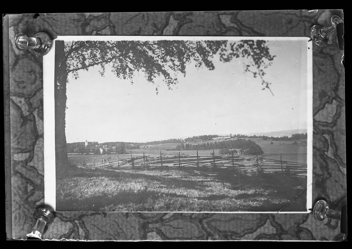 """Reprofotografi av ett foto föreställande ett landskap med en gärdesgård och ett träd i förgrunden och en liten kyrkby i bakgrunden. I fotografens anteckningar står det """"Rep. för Ing.[enjör] Bergs jungfru""""."""