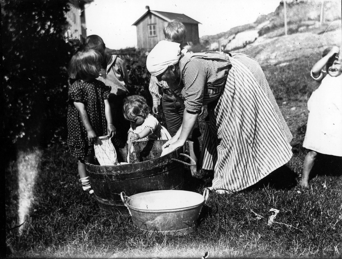 Kvinna tvättar tillsammans med fem barn, flickor och pojkar.