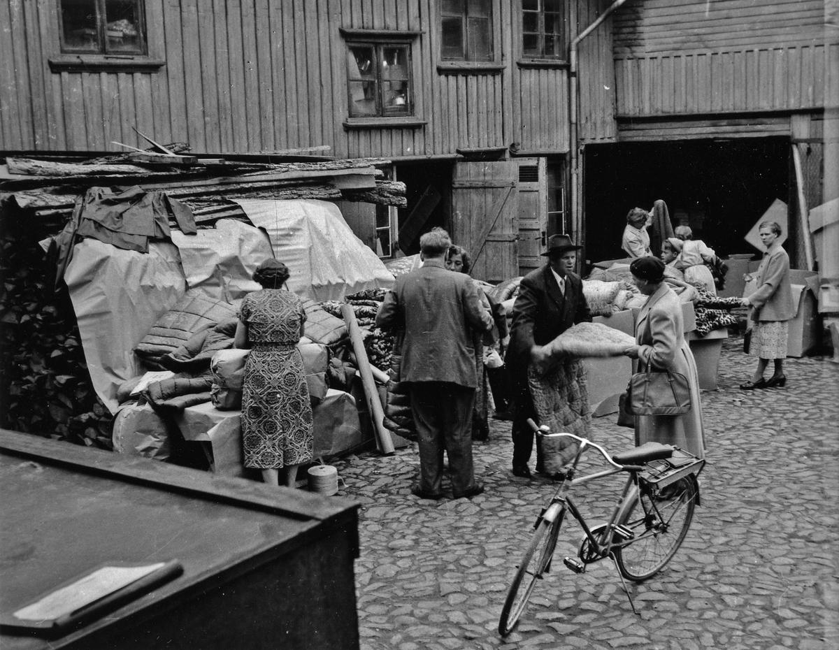 Kvinnor och män inspekterar auktionsföremål under auktion på gården till Tells hus på Kungsgatan 38. I förgrunden en cykel. Kvarteret Jägaren 11.