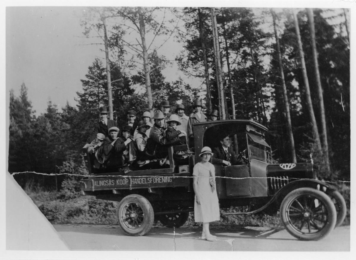 """Gruppbild av 15 kvinnor och män. En man sitter i flakbilens förarsätte och en kvinna står vid sidan av, resterande 13 sitter i flaket på flakbilen. På sidan av flaket står """"ALINGSÅS KOOP HANDELSFÖRENING""""."""