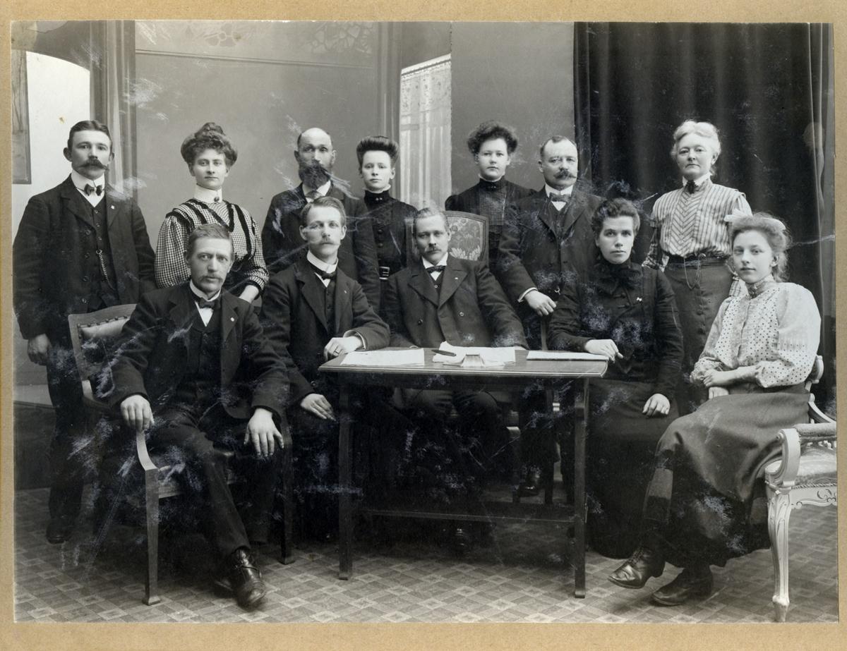 Gruppbild av 5 kvinnor och 6 män, sittande och stående, i en halvcirkel vända mot kameran. Främst ett litet arbetsbord med pappershögar och penna. Kommitté för nykterhetskurs, år 1909.  Stående från vänster:  Herr Ander Snickare Larsson Fröken Östergren (gift Norén)  Målarmästere Hinze Fru Mothéus  Sittande från vänster:  Kakelugnsmakare J.A. Jonsson Skräddare Jakobsson Handlare K.P. Wessman Fröken Lina Larsson Fröken Matheus