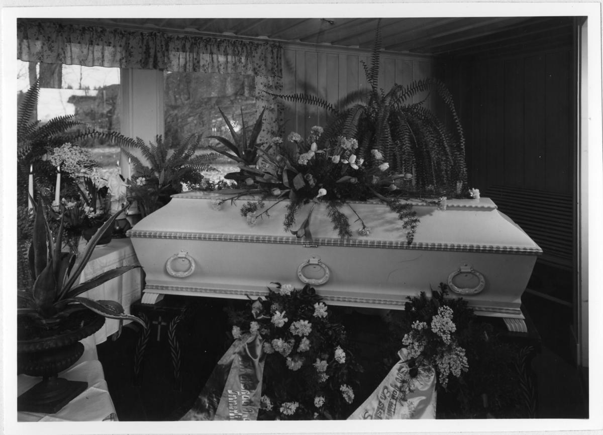 En kista täckt med begravningsblommor, en liten statyett av Jesus står i fönsterkarmen.  Begravning år 1947 i Alingsås.