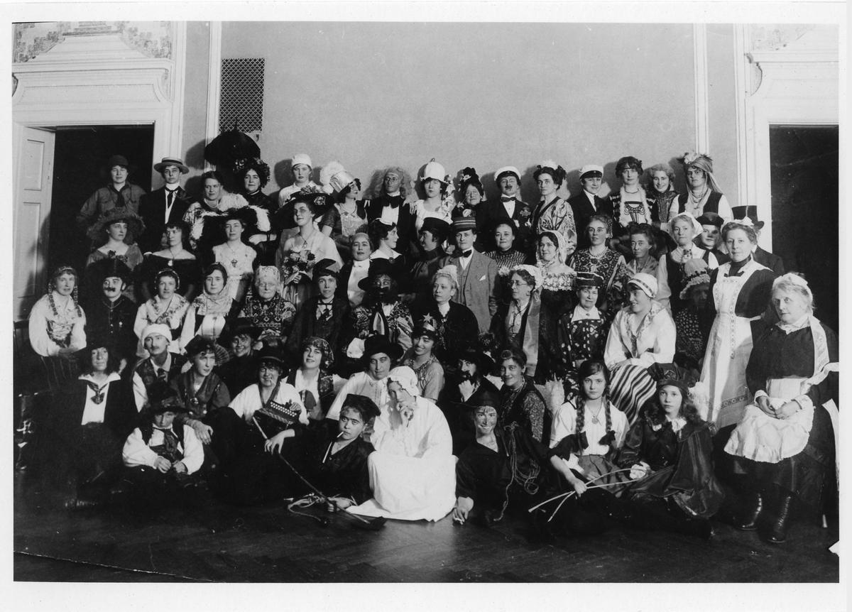 Gruppbild tagen på Stadshotellet med ett 60-tal kvinnor, i olika åldrar, i maskeradutstyrslar.