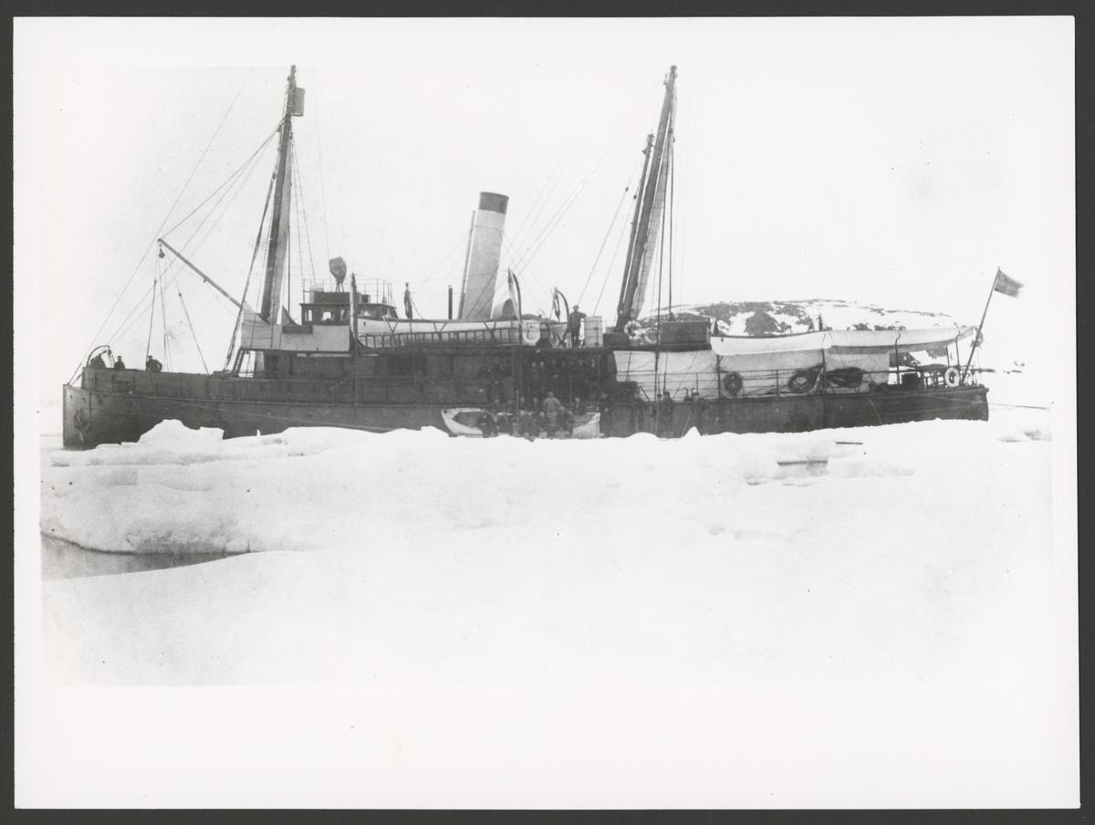 Bilden visar kanonbåten Svensksund som ligger mellan stora isflak framför kusten av Spetsbergen från babordssida. En av räddningsbåtar ligger midskepps på isen. Manskapet är uppställt i båten och vid relingen för fotografering.