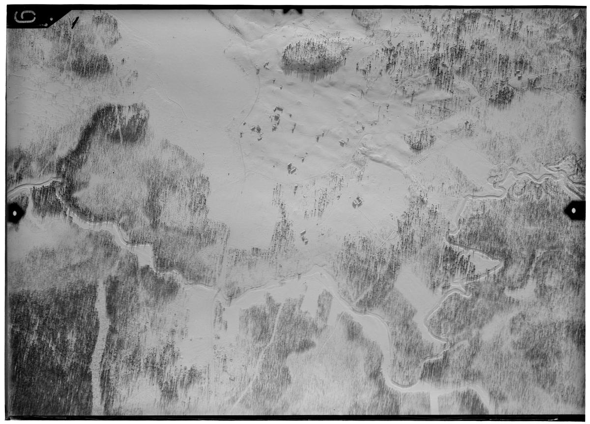 Flygfotografi av landskap kring Märkäjärvi i norra Finland under finska vinterkriget, 1940. Spaningsbild över skog, å och byggnader tagen av flygare vid F 19, Svenska frivilligkåren i Finland.