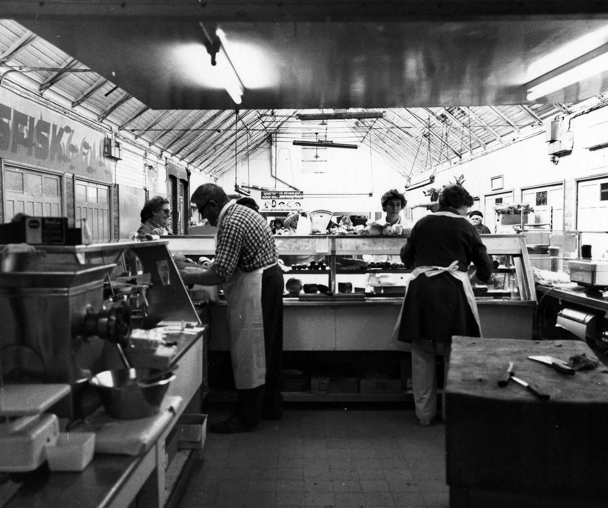 Bilden är tagen innifrån Saluhallen bakom disken till Rabnors Charkuteri. En man och en kvinna ses betjäna kunder. Kvarteret Gustaf.